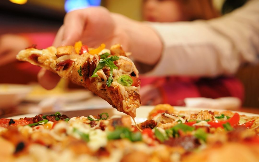 Woman picking up a slice of pizza.